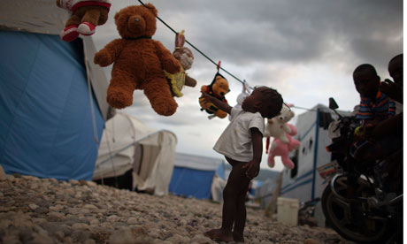A homeless Haitian child reaches out for a stuffed animal