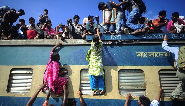 Eid al-Fitr: Dhaka, Bangladesh: People climb onto trains at the airport railway terminal