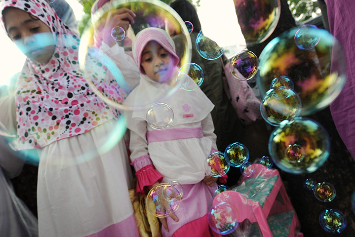 Eid al-Fitr: Jakarta, Indonesia: Children look at bubbles at a toy stall