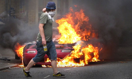 Masked man walks past a burning car outside a Carhartt store in Hackney on August 8, 2011