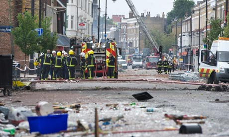 Firemen work on Tottenham High Road, in north London