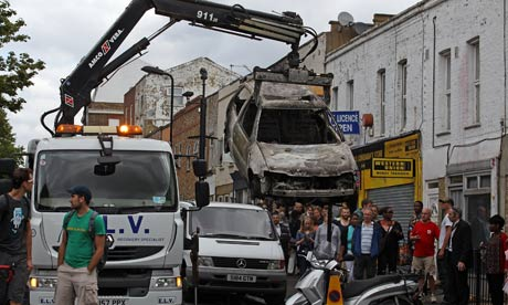 xRiots: Burnt out cars are removed from a residential street in Hackney
