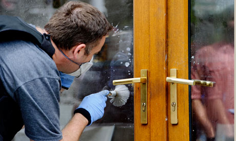 A police forensic officer takes fingerprints from a damaged shop in Ealing