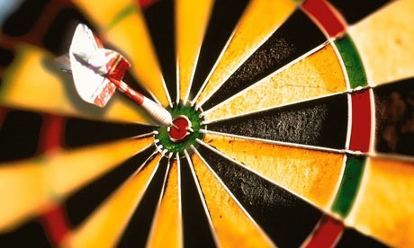 dart hitting dart board bulls eye