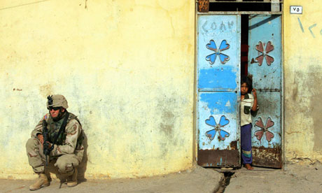 Iraqi girl stands in doorway as a US soldier patrols in Mosul, northern Iraq