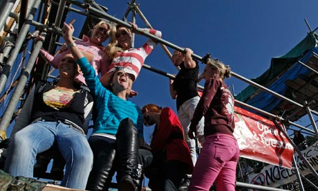 Travellers sit on a scaffolding forming part of a blockade at the Dale Farm site