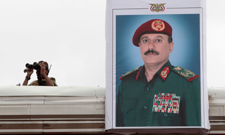 A soldier stands near a poster of Yemen's President Saleh during a military parade