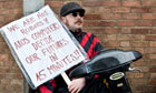 A protester demonstrates outside a work capability assessment office run by Atos