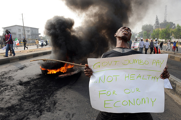 Nigeria fuel protests: A man carries a placard during a demonstration