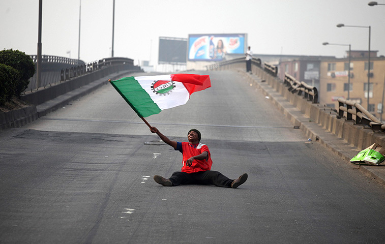 Nigeria fuel protests: A protester waves a flag on an empty road
