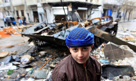 A Syrian boy stands in front of a damaged armoured vehicle belonging to the Syrian army in Homs