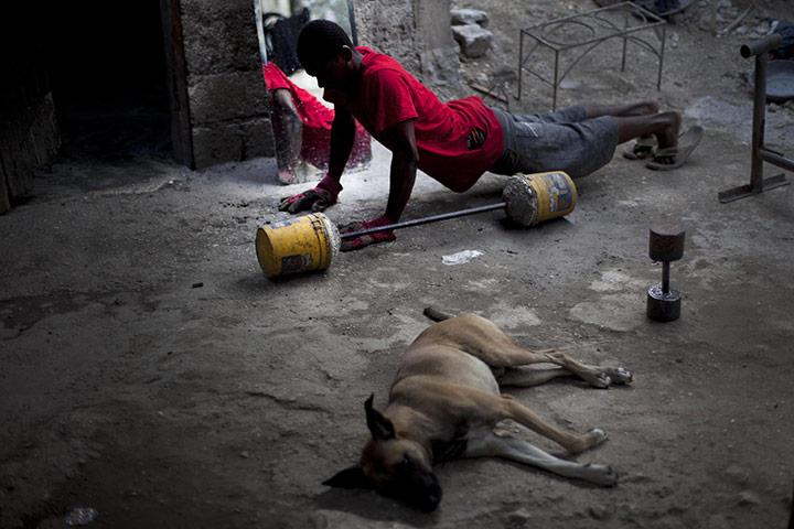 Порт-о-Пренс, Гаити: молодой человек упражняется у входа в свой дом