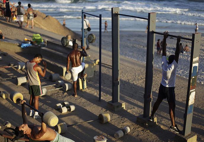 Рио-де-Жанейро, Бразилия: парни качаются на бесплатных тренажерах у пляжа Диабо