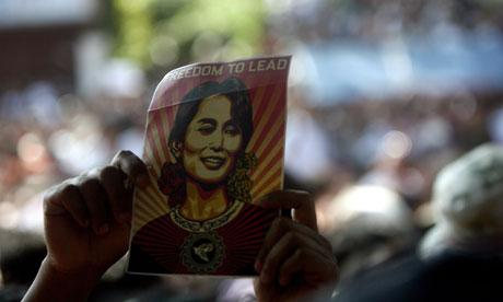 A supporter of Aung San Suu Kyi holds up a card with her picture.