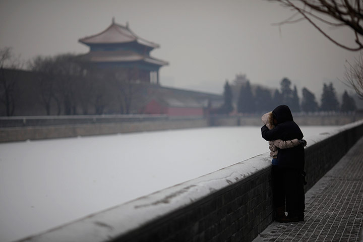 24 Hours: A man and woman kiss outside of the Forbidden City in Beijing