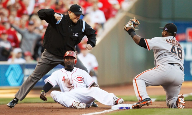 San Francisco Giants third baseman Pablo Sandoval (R) tags out Cincinnati Reds' Brandon Phillips as he tries to take third base on a passed ball while third base umpire Chad Fairchild (L) makes the call during the first inning of Game 3 in their MLB NLDS playoff baseball series in Cincinnati, Ohio, October 9, 2012.  REUTERS/Jeff Haynes (UNITED STATES  - Tags: SPORT BASEBALL) :rel:d:bm:TB3E8A91RHC80