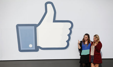 Girls pose in front of Facebook sign