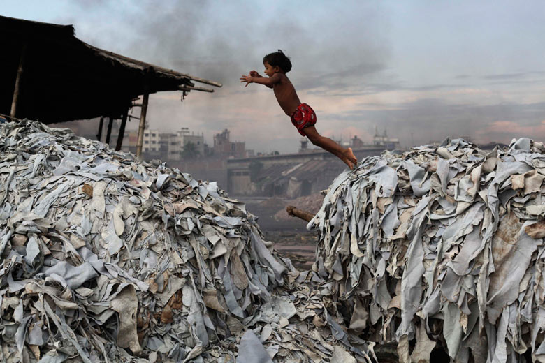 A child jumps on the waste products as she plays in a tannery in Dhaka