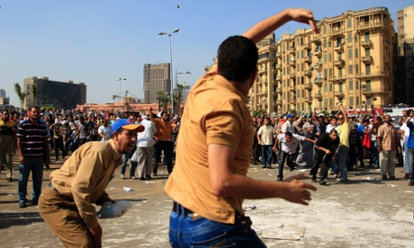 A protester throws a stone after scuffles broke out between groups of several hundred protesters in Tahrir Square when chants against the new Islamist president angered some in the crowd in Cairo, today. Photograph: AP/Khalil Hamra