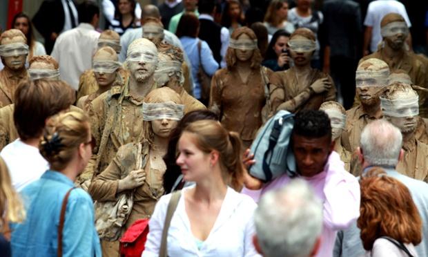 Street artists perform a piece called Blind on Avenida Paulista in São Paulo, Brazil