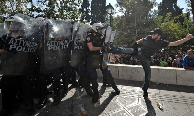 A demonstrator clashes with riot police during a 24-hour strike in Athens. The protesters had broken through a police line outside luxury hotels on central Syntagma Square.