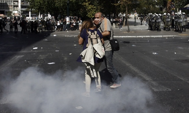 Greek demonstrators protect themselves from tear gas.