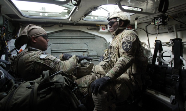 US soldiers PFC Small Kyle (left) and SPC Josias Tchouasse prepare to leave their armoured vehicle to provide security during a meeting among local Afghan government officials, village leaders and the US army in Arghandab river valley in Kandahar province, Afghanistan