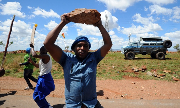 An angry striking miner brandishes a rock as he marches along with thousands of others to the offices of Anglogold Ashanti in Carletonville, South Africa. Thousands of miners returned to work today, just hours before a deadline to end their strike or face dismissal, but many look set to continue their industrial action