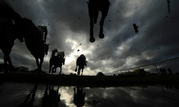 Under a forbidding sky runners take the water jump in The Bathwick Tyres Yeovil Handicap Steeple Chase at Wincanton racecourse in England.