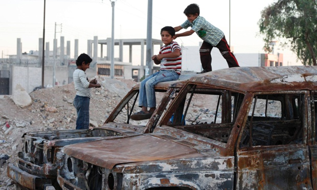 Children play on burnt cars in Aleppo.