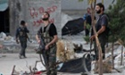 Free Syrian Army fighters hold their weapons as they look at a jet in the sky above Aleppo's Bustan al-Basha district.