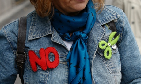 A demonstrator wears badges symbolizing no cuts during a protest by civil servants against government austerity measures in Madrid.