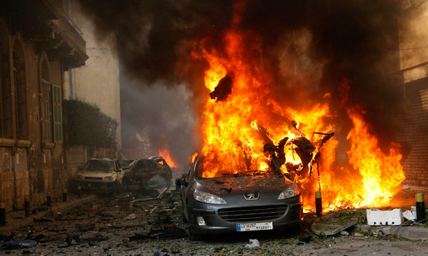 A car burns at the site of an explosion in Beirut