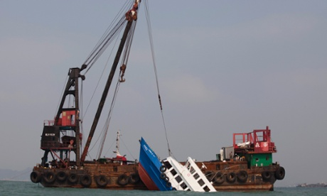 A sunken ferry is lifted out of the water after a collision off Hong Kong