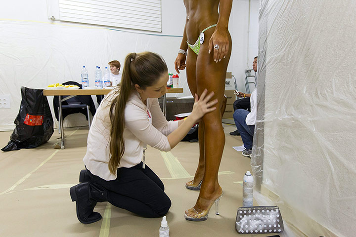Bodybuilding: A female bodybuilder is painted prior to going on stage