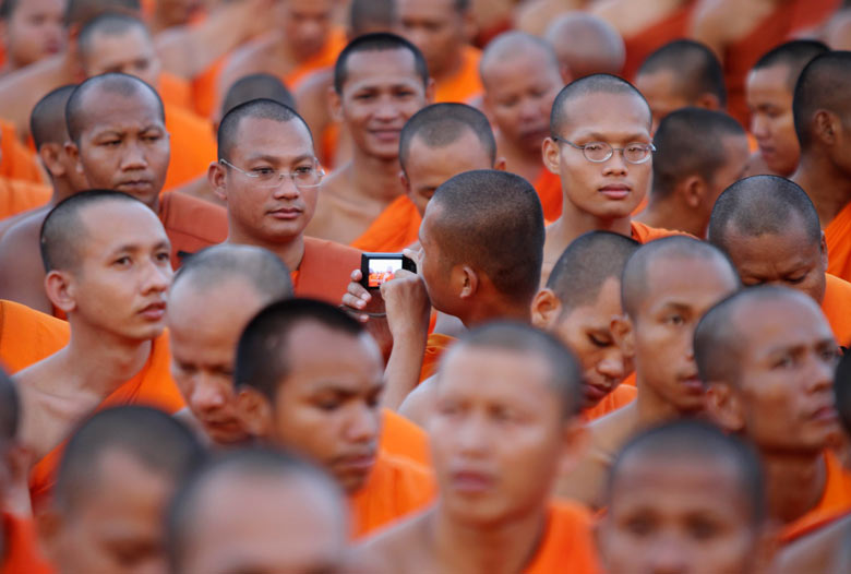 A Cambodian Buddhist monk takes pictures during a ceremony in front of the Royal Palace, Phnom Penh