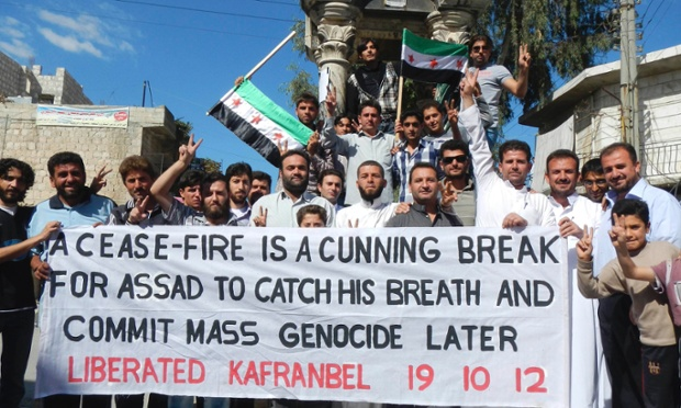 Protesters in the rebel stronghold of Kafranbel, Idlib express hold a banner expressing their suspicions about a ceasefire with the Assad government.