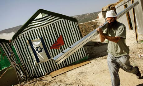 A Jewish settler carries bars for a house he is building in the West Bank