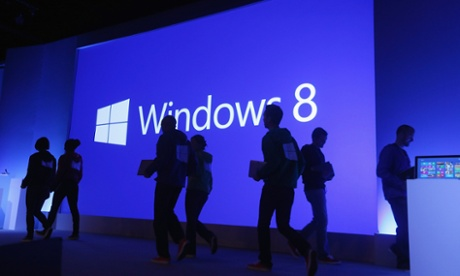 People walk past a display at a press conference unveiling the Microsoft Windows 8 operating system in New York.