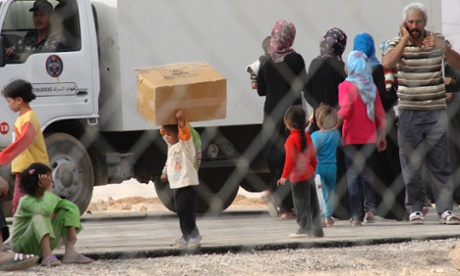 Syrian refugees, who fled the unrest in Syria, receive humanitarian aid ahead of Eid al-Adha at the Al Zaatri refugee camp in the Jordanian city of Mafraq.
