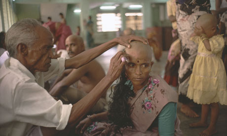 A woman donates her hair for auction at the Tirumala temple in India
