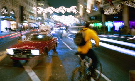 cyclist in front of a car in city street at night