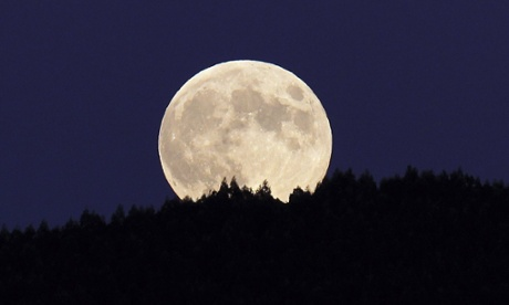 A view of the full moon rising over a wood near Bilbao, northern Spain.