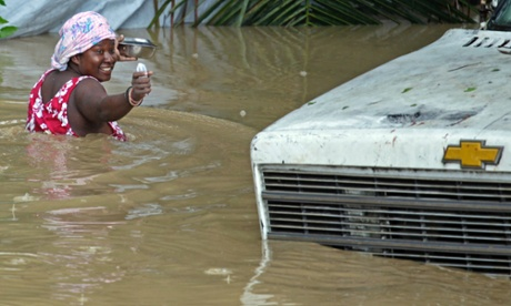 A resident of Leogane, Haiti makes her way to her home as the water level continues to rise on 26 October 2012. Photograph: Carl Juste/AP