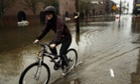 A woman rides her bicycle through a flooded street in the Red Hook section of Brooklyn after Hurricane Sandy caused extensive damage in the area.