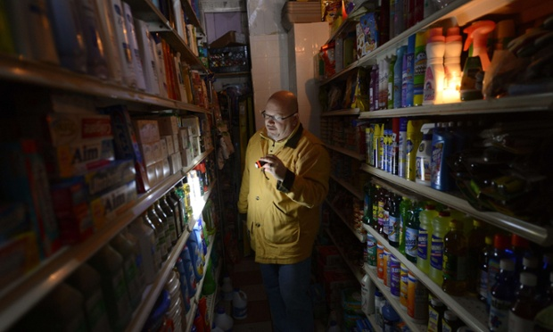 A man shops for groceries by flashlight at an East Village grocery store in New York as New Yorkers cope with the aftermath of Hurricane Sandy. The storm left large parts of New York without power and transportation.