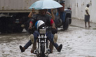 Locals ride a motorbike in a flooded street in Santo Domingo, Haiti