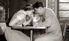 1950s 1960s Laughing Teenage Boy and Girl Sharing Drink Together With Two Straws In Soda Shop