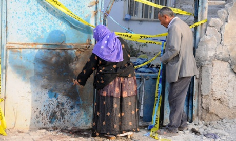 Turkish local residents check a house which was hit by a mortar bomb fired from Syria in Akcakale.