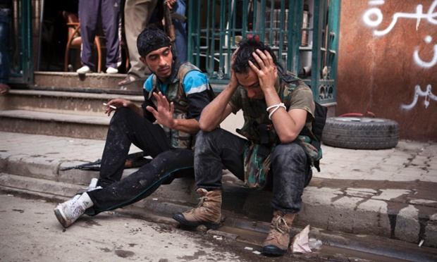 A Free Syrian army figther cries after one of his friends was injured during fighting with the Syrian Army, outside the Dar El Shifa hospital in Aleppo, Syria.